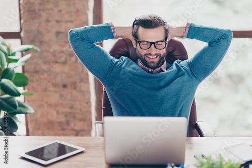 Deurstickers Ontspanning Stunning, harsh, virile, joyful man holding two hands behind the head, watching movie, video on laptop, having fun during break time, looking at screen of computer, sitting at desk in work place