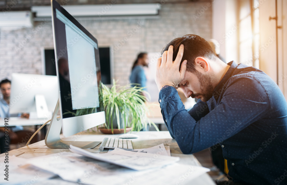 Fototapeta Portrait of overworked employee in modern office