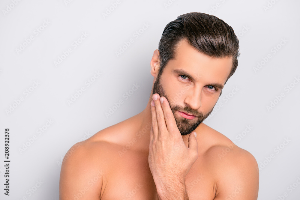 Fototapeta Attractive, brutal, modern, manly, virile, confident, dreamy, naked man touching his perfect, ideal face skin, holding hand on beard, cheek, looking at camera, isolated over gray background