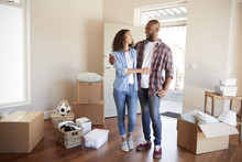 Happy Couple Surrounded By Boxes In New Home On Moving Day