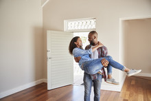 Man Carrying Woman Over Threshold Of Doorway In New Home