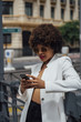 Beautiful Afro hair girl with mobile phone in the streets of Madrid Spain