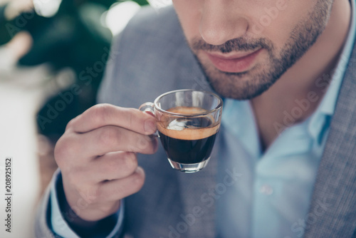Canvas Print Cropped close up half face portrait of stylish attractive man holding small glas