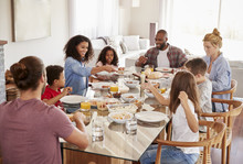 Two Families Enjoying Meal At Home Together