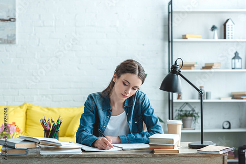 Obraz concentrated teenage girl writing and studying at desk at home - fototapety do salonu