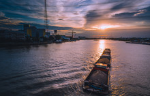 BANGKOK, THAILAND - 2018 JUNE 6: The Tug Boats Towing A Big Barge With Sand. Cargo Ship In A River. In Chao Phraya River, Bangkok Thailand Under The Beautiful Sunset Sky. Rama VII Bridge In Bangkok.