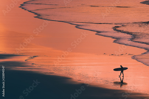 Poster Corail distant surfer silhouette in the shore at sunset