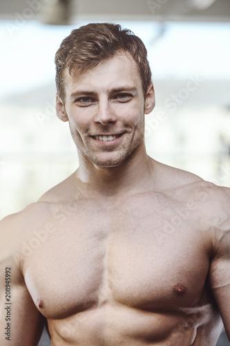 Fotografie, Obraz  handsome strong bodybuilder athletic men pumping up muscles with dumbbells