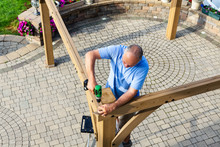 Man Building A Wooden Gazebo On A Brick Patio
