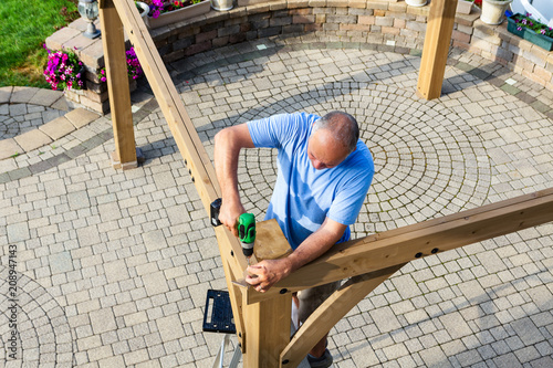 Man building a wooden gazebo on a brick patio Obraz na płótnie