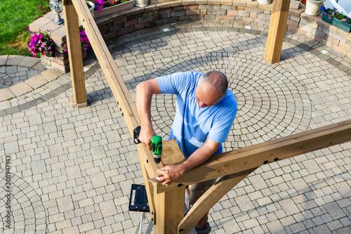 Fotografie, Tablou Man building a wooden gazebo on a brick patio