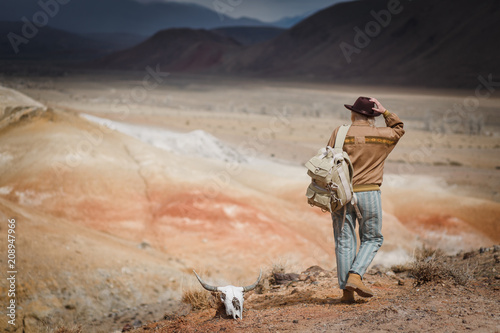 Valokuva  Beautiful young girl in hare, hat and with backpack travels among sands in wild