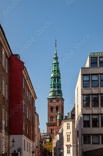 Photo  old tower with tall spire and historical buildings on street in copenhagen, denm