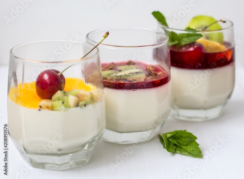 Vászonkép dessert of fruit cream with cherries and mint on white background