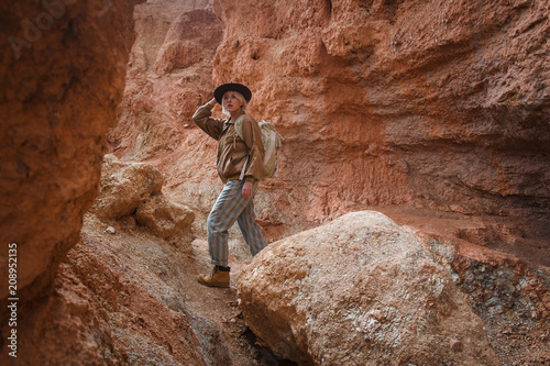 Foto  Beautiful young girl in hare, hat and with backpack travels among sands in wild