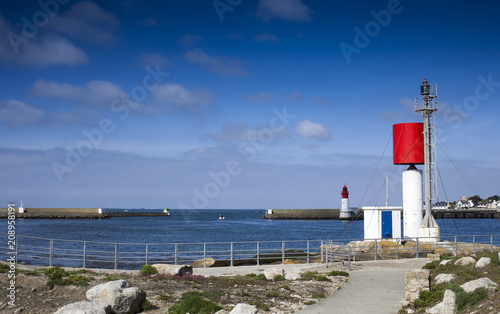 Foto op Plexiglas Poort Small lighthouses at the main entrance of the big harbor of Guilvinec village, Brittany, France, early in the morning