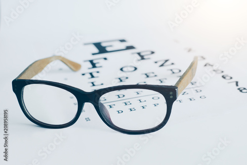 Photo  Eyeglasses on an optician visual text chart with white background