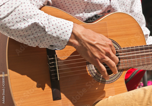 Fotografia, Obraz  Front view, close up of a spanish young man's hand strumming the strings of a wo