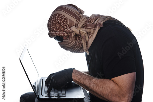 Fotografía  The man hidden under the arafatka and black glasses keeps his hands in black gloves on the laptop