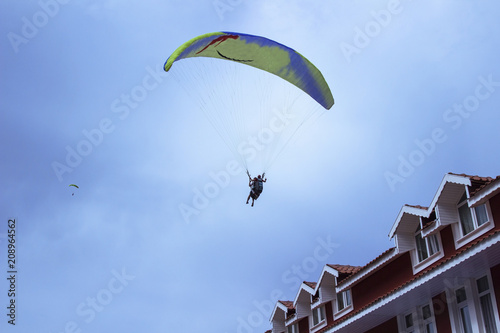 Foto op Aluminium Luchtsport Skydiver against the blue sky and the roof of the house