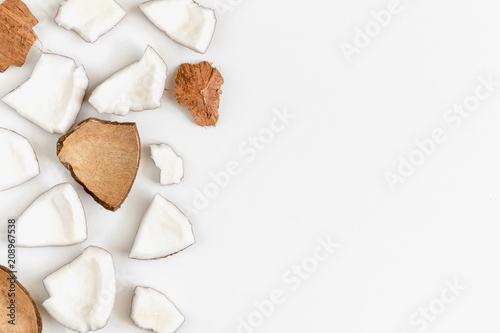 Pieces of coconut on white background. Flat lay, top view, copy space