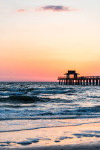 Naples, Florida Pink And Orange Sunset Vertical View In Gulf Of Mexico With Sun Setting Inside Pier Wooden Jetty, Horizon And Dark Blue Ocean Waves
