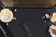 Popcorn, Snack And A Remote Control For The TV, Top View And Flat Lay On Black Background