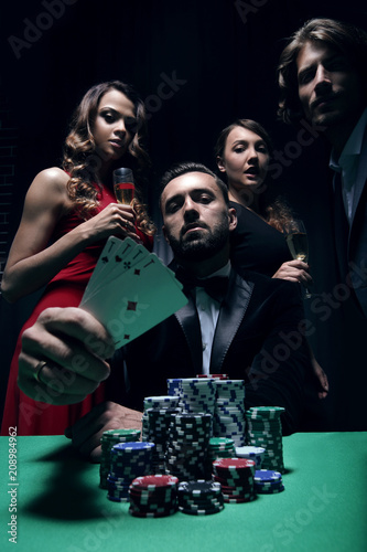 фотография  concentrated men and women playing poker in casino