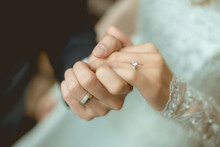 The Couple Holding Hands Together. They Had A Wedding Rings Wear Their Fingers.