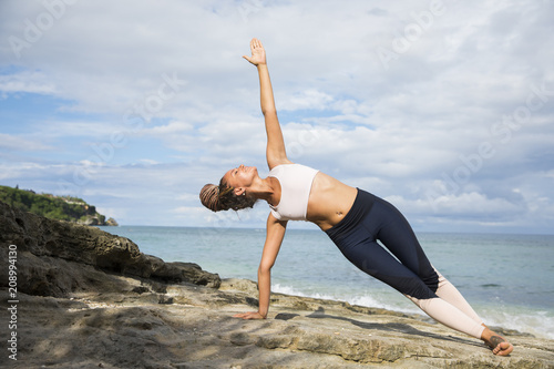 Woman stretching and posing at seaside