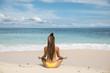 Woman in bikini meditating at seaside