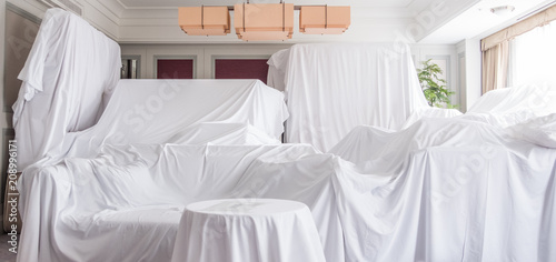 Fotografía  White dust cover cloth covering furnitures in a room