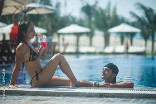 Young couple relaxing in the pool at the resort Poster