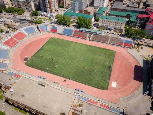 Láminas  Aerial photography of a modern  stadium with green field for football, a big road, city traffic and parks on a warm summer day