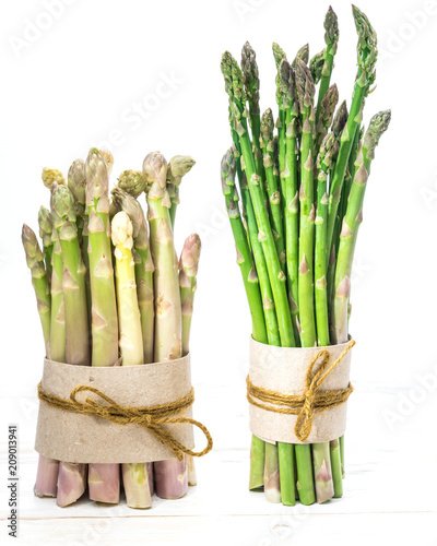 Photo Bundles of green and white asparagus on wooden board