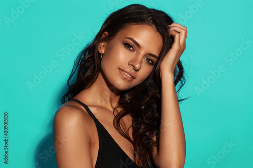 Young sexy slim tanned woman in black swimsuit posing against blue background Wallpaper Mural