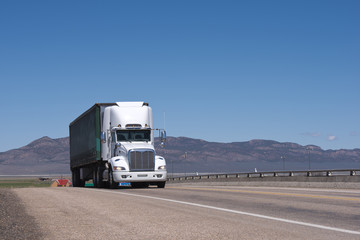 White American big rig semi trick with spoiler on the roof transporting covered semi trailer on the road in Utah