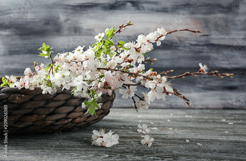 Basket with blooming flowers on wooden table