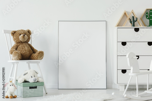 Teddy bear on white chair next to white poster with mockup in child's room interior. Real photo. Place for your graphic
