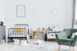 Bright scandinavian style bedroom interior with two metal frame kid's beds, one white, one black, and green armchair for caretaker. Posters of a rabbit and an elephant on white wall. Real photo