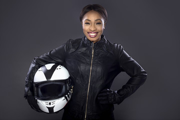 Black female motorcycle biker or race car driver or stuntwoman wearing leather racing suit and holding a protective helmet.  She is standing confidently in a studio