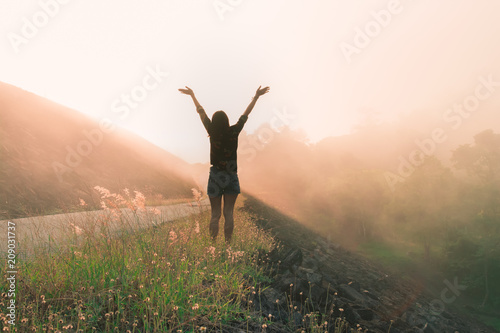 Fotomural  Back view of young woman raise arms with beautiful morning sunrise landscape, travel around the world concept