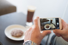 Close Up Man Hand Holding Mobile Smartphone Taking Picture Of Breakfast  Soft Cookie Black Coffee On Wooden Table.