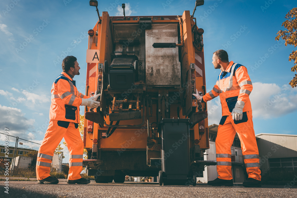 Fototapeta Two refuse collection workers loading garbage into waste truck emptying containers