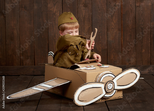 Fototapeta  children boy are dressed as soldier in retro military uniforms repair an airplan