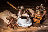 Fototapeta Kawa jest smaczna - high angle view of coffee cup with vintage cezve and coffee grinder on rustic wooden table spilled with roasted beans