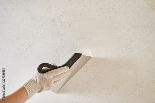 Fotomural  Spatula with putty in hand. Worker puts of plaster on wall.