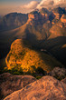 Dramatically lit portrait of the Three Rondavels and mountains with foreground rock at sunset golden hour. Mpumalanga, South Africa.