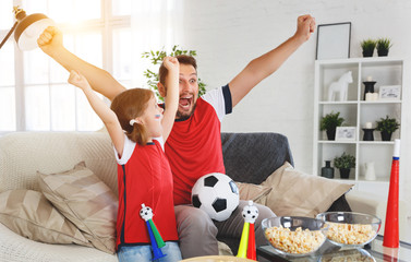 Obraz family of fans watching a football match on TV at home