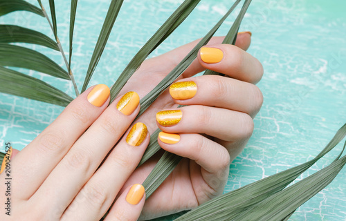 Female hands with orange nail design Wallpaper Mural